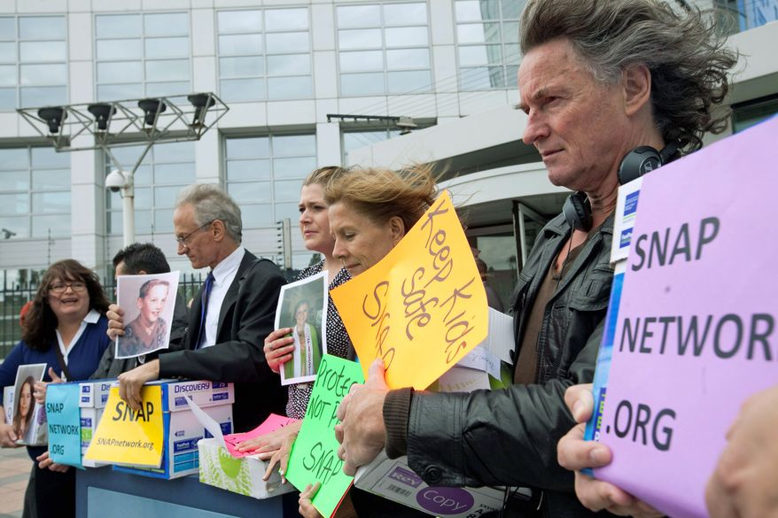 """Members of Survivors Network of those Abused by Priests (SNAP) state their case in front of the International Criminal Court in The Hague on Tuesday. They want an investigation of high Vatican officials for possible crimes against humanity involving the coverup of the """"long-standing and pervasive system of sexual violence"""" despite promises to swiftly oust predators. (Associated Press)"""