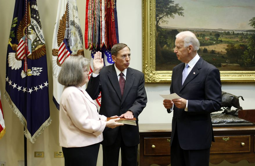 Vice President Joseph R. Biden Jr. (right) administers the oath of office to David H. Petraeus during Mr. Petraeus' swearing-in ceremony as CIA director on Tuesday, Sept., 6, 2011, in the Roosevelt Room of the White House in Washington. Holding the Bible is Mr. Petraeus' wife, Holly Knowlton Petraeus. (AP Photo/Pablo Martinez Monsivais)