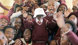 Ontlametse Phalatse stands on a desk surrounded by classmates at the Lorato Primary School in Hebron, South Africa. The 12-year-old has a rare condition called progeria, a genetic premature-aging disease. While she has proved to be a bright pupil at Lorato, she was often scorned because classmates and teachers thought she had AIDS. (Associated Press)