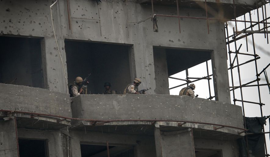 Afghan security forces are seen in a high-rise building during a gunbattle with al-Qaeda- and Taliban-affiliated Haqqani militants in Kabul, Afghanistan, on Wednesday, Sept. 14, 2011. (AP Photo/Musadeq Sadeq)