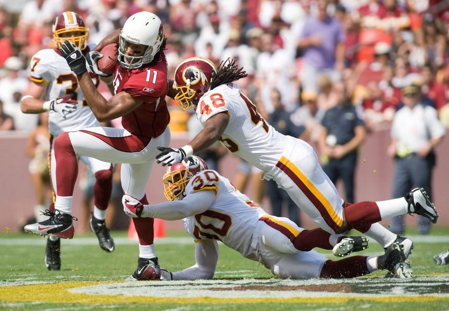 Larry Fitzgerald (11) of the Arizona Cardinals is en route to an 18-yard gain against the Washington Redskins in a 2008 game as safety LaRon Landry (30) and former Redskin Chris Horton (48) try to stop him. Washington again faces the task of containing the Pro Bowl wide receiver Sunday. (The Washington Times)