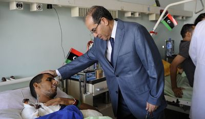 Libyan National Transitional Council Prime Minister Mahmoud Jibril speaks with a patient at the Tripoli Medical Center in Tripoli, Libya, on Thursday, Sept. 15, 2011. (AP Photo/Eric Feferberg, Pool)