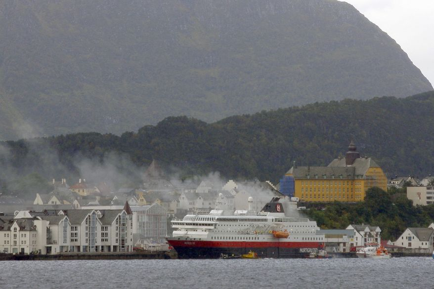 Smoke rises from the Norwegian cruise ship MS Nordlys, shown docked in Alesund, Norway, on Thursday, Sept. 15, 2011. A fire that broke out in the engine room killed two crew members, but all 207 passengers were taken to safety. (AP Photo/Scanpix)