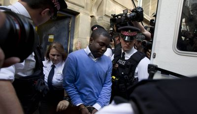 Alleged renegade UBS trader Kweku Adoboli (center) walks Sept. 16, 2011, to a security van flanked by police officers after appearing at the City of London Magistrates Court in London. (Associated Press)