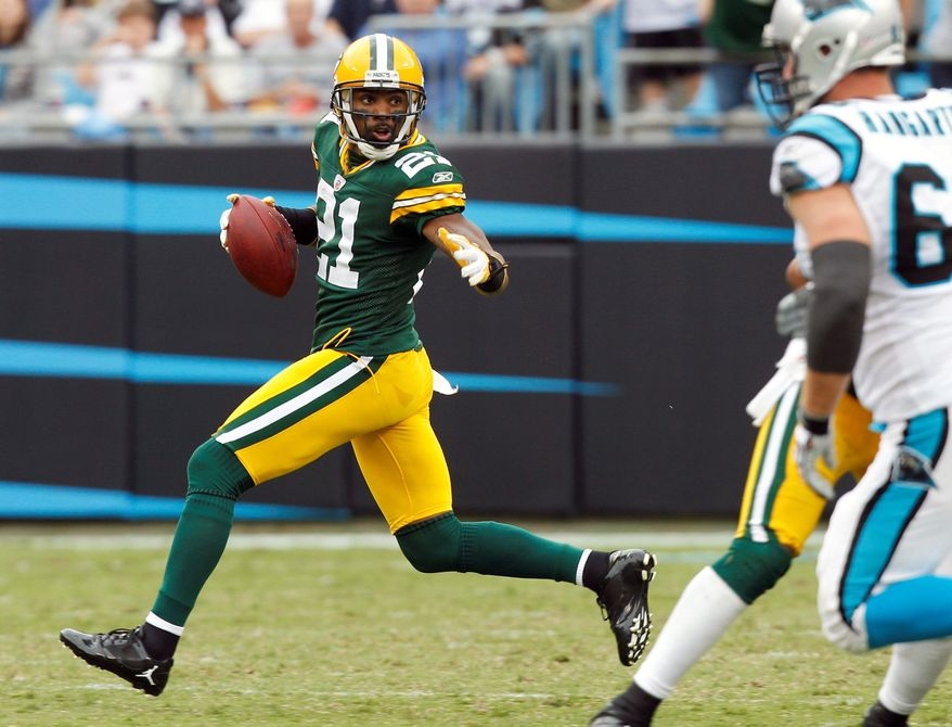 The Green Bay Packers' Charles Woodson (21) runs after intercepting a Carolina Panthers pass during the third quarter of an NFL football game in Charlotte, N.C., on Sunday, Sept. 18, 2011. (AP Photo/Chuck Burton)