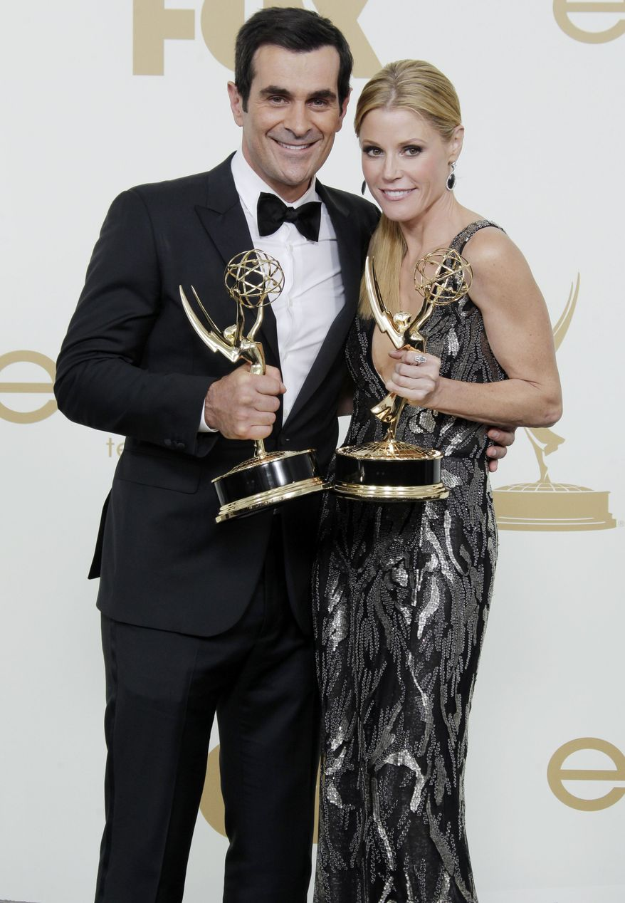 "Ty Burrell (left) and Julie Bowen from the television series ""Modern Family"" hold their Emmys for best supporting actor and actress in a comedy backstage at the 63rd Primetime Emmy Awards on Sunday, Sept. 18, 2011, in Los Angeles. (AP Photo/Jae Hong)"