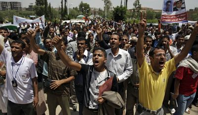 """Students shout slogans as they protest on the Sanaa University campus in Sanaa, Yemen, on Sunday, Sept. 18, 2011, to show their support of a boycott of university studies as part of demonstrations demanding the resignation of Yemeni President Ali Abdullah Saleh. The Arabic on the billboard reads, """"The resumption of school before dropping the regime is betrayal to the blood of the martyrs."""" (AP Photo/Hani Mohammed)"""