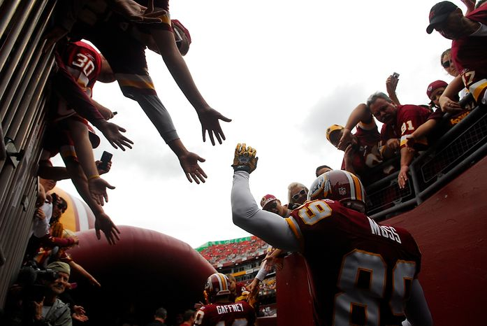 Washington Redskins wide receiver Santana Moss greats fans as he heads onto the field to face the Arizona Cardinals at FedEx Field in Landover, Md., on Sunday, Sept. 18, 2011. (Andrew Harnik/The Washington Times)