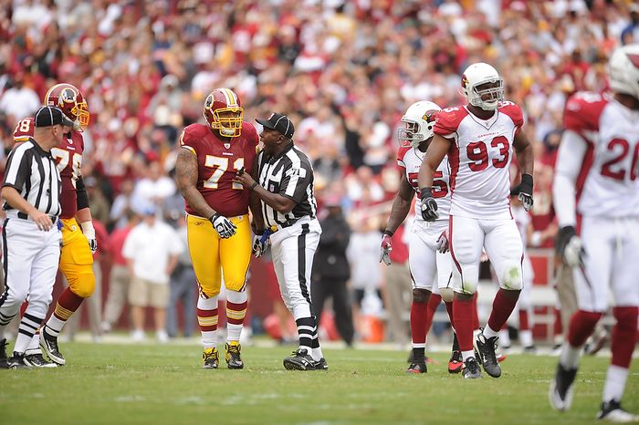 Umpire Ruben Fowler (center) talks with Washington Redskins offensive tackle Trent Williams after a first-quarter play against the Arizona Cardinals at FedEx Field in Landover, Md., on Sunday, Sept. 18, 2011. (Andrew Harnik/The Washington Times)