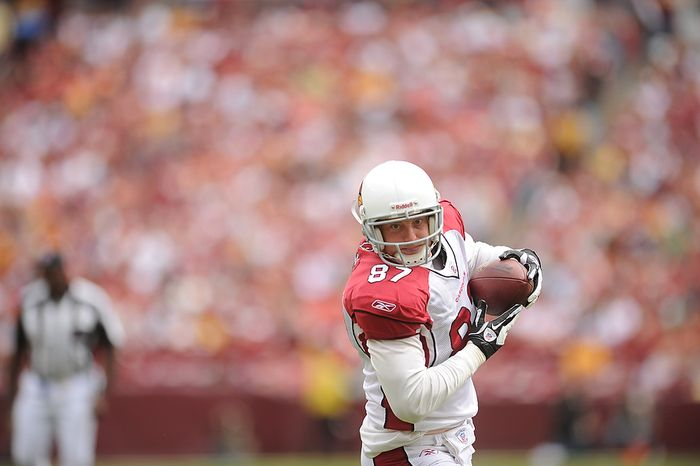 Arizona Cardinals quarterback Kevin Kolb (not shown) throws a 21-yard touchdown pass to tight end Jeff King (foreground) during the first quarter of a game with the Washington Redskins at FedEx Field