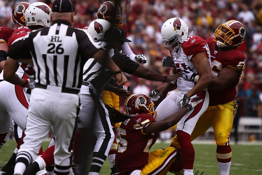 Redskin running back and former Cardinal Tim Hightower gets into a scuffle after putting a late block on Arizona Cardinals' linebacker Paris Lenon during the first quarter at FedEx Field in Landover, Md., on Sunday, September 18, 2011. (Pratik Shah/The Washington Times)