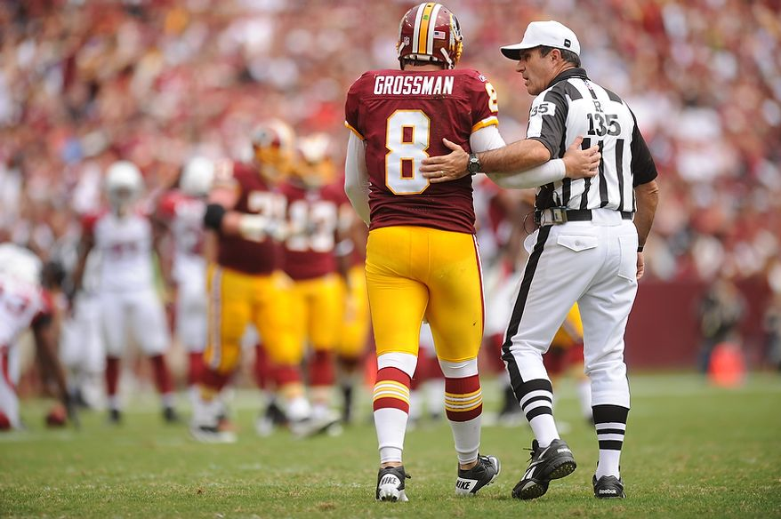 Referee Pete Morelli checks on Redskins' quarterback Rex Grossman after he was knocked down by Arizona Cardinals strong safety Adrian Wilson (24), during the third drive of the first quarter at FedEx Field in Landover, Md., on Sunday, September 18, 2011. (Andrew Harnik/The Washington Times)