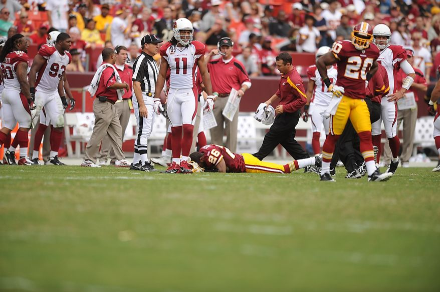 Redskins' trainers come to the aid of cornerback Josh Wilson (26) after he was injured in the third quarter against the Arizona Cardinals at FedEx Field in Landover, Md., on Sunday, September 18, 2011. (Andrew Harnik/The Washington Times)