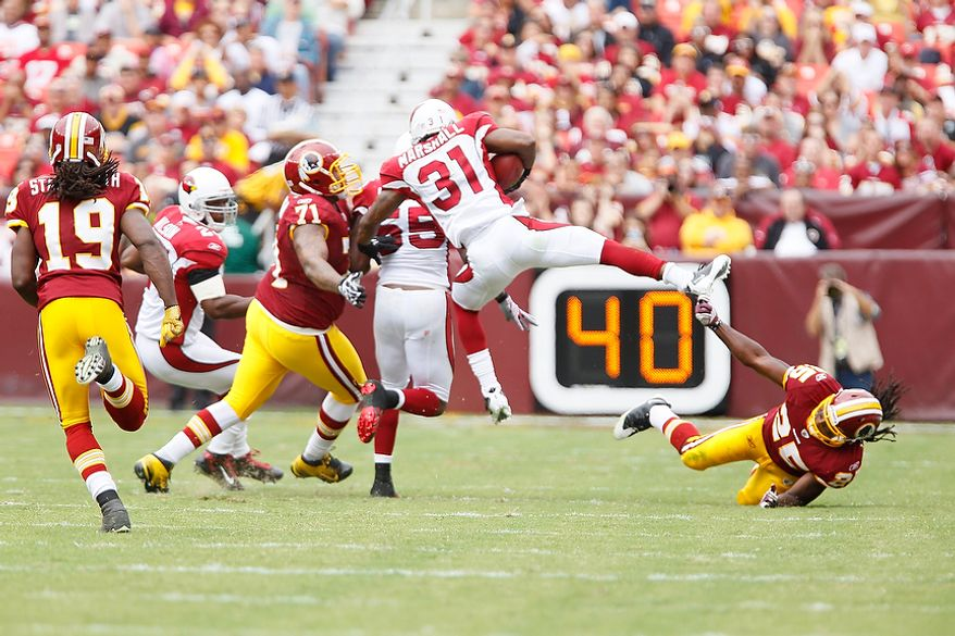Arizona Cardinals' cornerback Richard Marshall (31) is tackled by Redskins' running back Tim Hightower (25) and offensive tackle Trent Williams after he intercepted a pass from Redskins' quarterback Rex Grossman at the Arizona 39-yard line to kill the second Redskins' drive of the first quarter at FedEx Field in Landover, Md., on Sunday, September 18, 2011. (T.J. Kirkpatrick/The Washington Times)