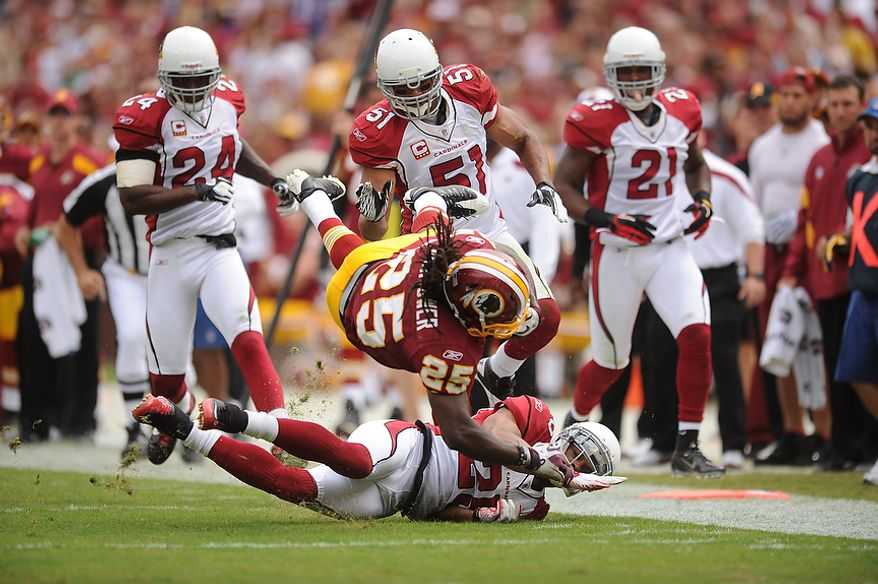 Redskins running back Tim Hightower (25) is taken dow by Arizona free safety Kerry Rhodes (25) after a 20-yard run in the second quarter to set up a touchdown against the Arizona Cardinals at FedEx Field in Landover, Md., on Sunday, September 18, 2011. (Andrew Harnik/The Washington Times)