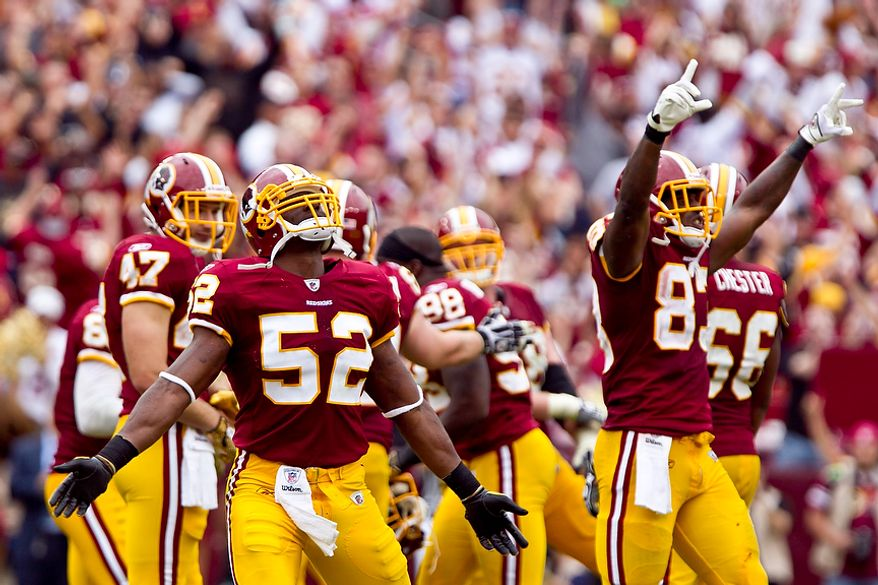 Washington Redskins linebacker Rocky McIntosh (52) and tight end Fred Davis (83) celebrate as the clock runs out on the fourth quarter as the Redskins beat the Arizona Cardinals 22-21 at FedEx Field in Landover, Md., on on Sunday, Sept. 18, 2011. (T.J. Kirkpatrick/The Washington Times)