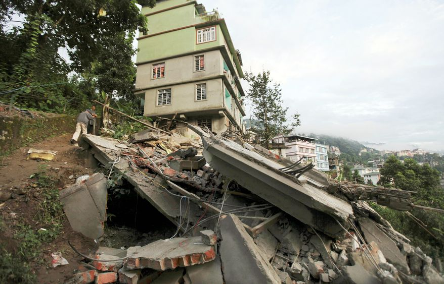Residents stand near the debris of a building that collapsed in Gangtok, India, the capital of Sikkim state in northeastern India, after the earthquake. The temblor killed people in Nepal, Tibet and India.