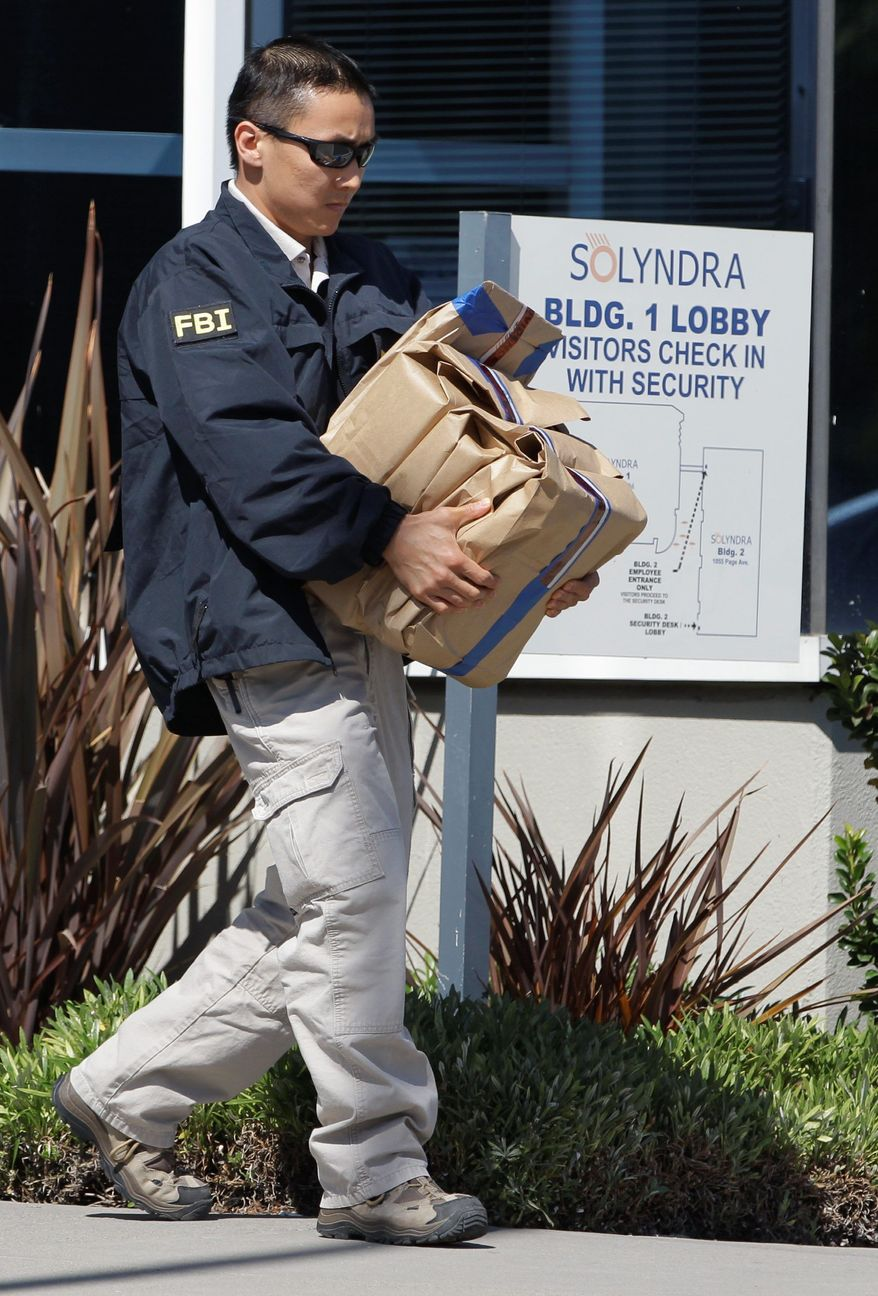 An FBI agent carries out evidence from Solyndra headquarters in Fremont, Calif., on Sept. 8 in a probe of its collapse after receiving $535 million in federal loans. (Associated Press)