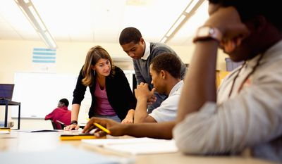 McKinley students (from left) Robert Shedrick Jr., Malik Harleston, and Ryan Sturdivant work through a math problem with Shira Fishman, the District's Teacher of the Year for 2011. (Andrew Harnik/The Washington Times)