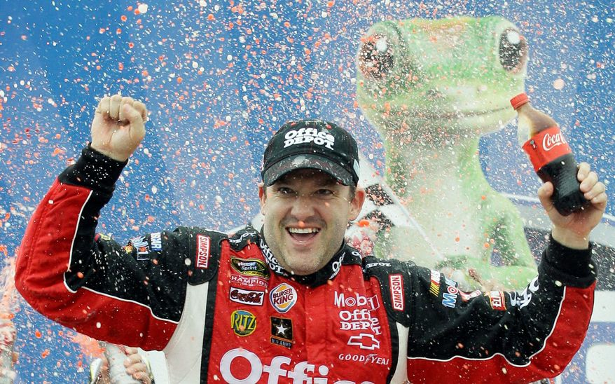 Tony Stewart celebrates after winning the Geico 400 at Chicagoland Speedway, his first Sprint Cup victory of the season. (Associated Press)
