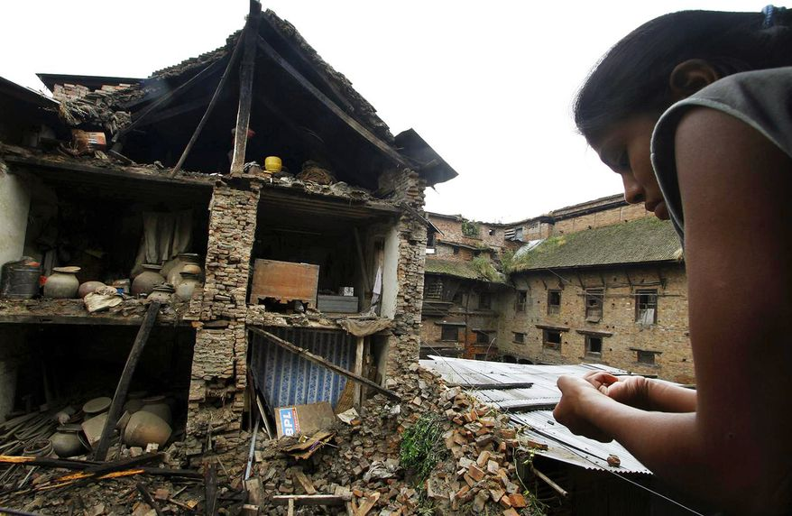 A woman looks out of a window in Katmandu, Nepal, on Sept. 19, 2011, at debris from collapsed buildings that were damaged the previous day by an earthquake that shook northeast India, Nepal and Tibet. (Associated Press)