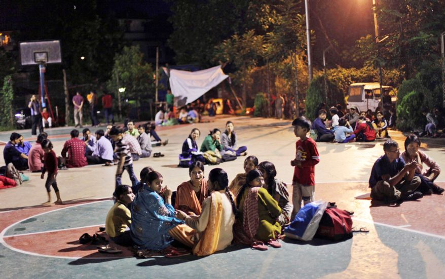 Residents fearing more aftershocks following Sunday's strong earthquake sit on a basketball court at a university in Gangtok, India, on Monday, Sept. 19, 2011. (AP Photo/Altaf Qadri)