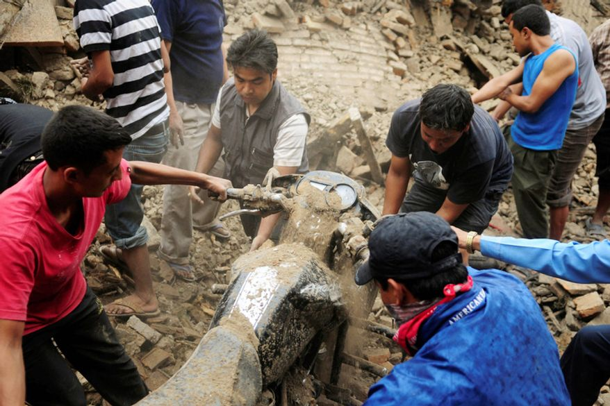 Nepalese remove a motorbike buried under the debris of a house damaged by Sunday's earthquake in Bhaktapur, Nepal, about 9 miles from Katmandu, the capital, on Monday, Sept. 19, 2011. (AP Photo)