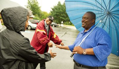Candidate Arthur Turner (right) greets voters Ricardo Lewis and his wife Sandra Livingston-Lewis (left) of Mitchellville, who arrived in the rain to vote. (Rod Lamkey Jr./The Washington Times)