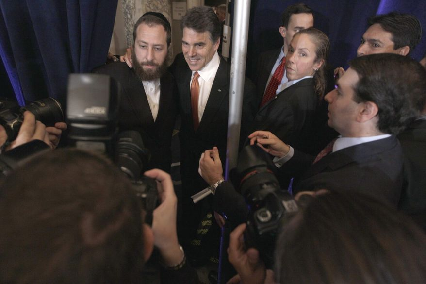Republican presidential candidate, Texas Gov. Rick Perry, second from left, poses for a photo with a supporter after a news conference in New York, Tuesday, Sept. 20, 2011. (AP Photo/Mary Altaffer)