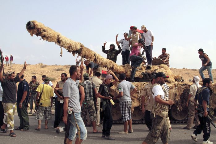 Libyan revolutionary fighters celebrate the capture of a tank from pro-Gadhafi forces in Sirte, Libya, on Tuesday, Sept. 20, 2011. (AP Photo/Gaia Anderson)