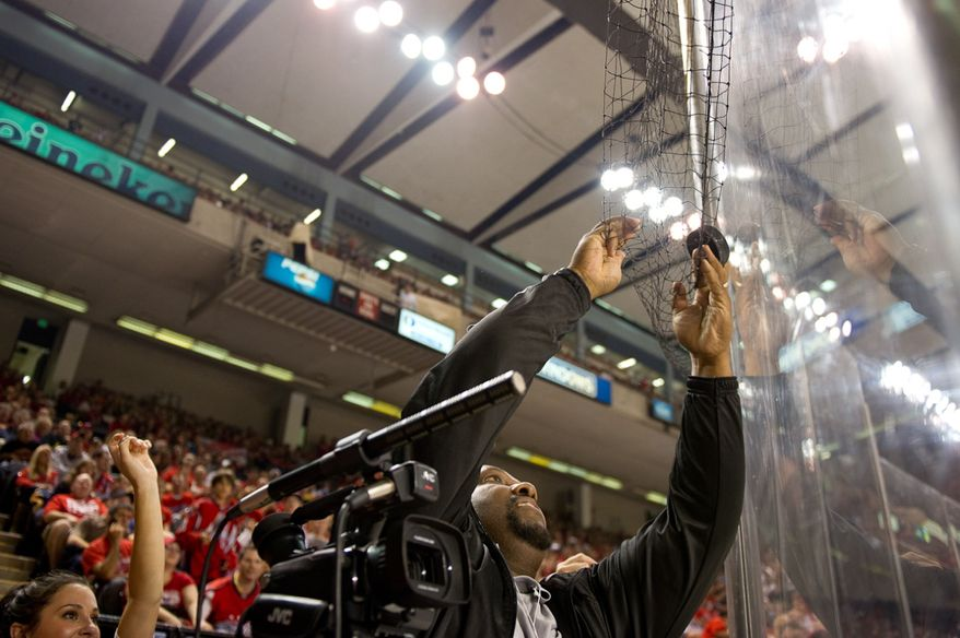 Baltimore Sun videographer Kevin Richardson grabs a puck out of play and refuses to give it to a fan in the third period of the Washington Capitals' 2-0 loss to the Nashville Predators in a preseason exhibition game at the 1st Mariner Arena in Baltimore on Sept. 20, 2011. (Andrew Harnik/The Washington Times)
