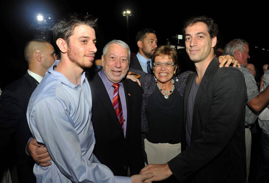 Freed American Josh Fattal (left) meets relatives and friends upon his arrival in Muscat, Oman, from Tehran on Wednesday, Sept. 21, 2011. After more than two years in Iranian custody, he and fellow American Shane Bauer, convicted as spies, took their first steps on their way home as they bounded down from a private jet and into the arms of family for a joyful reunion in the Gulf state of Oman. (AP Photo/Sultan Al-Hasani)