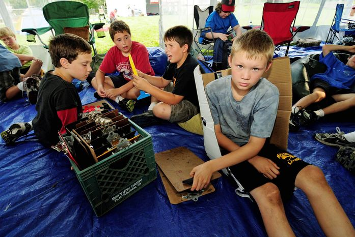 "Associated Press Sixth-grader Colin Green, 11, grabs a clipboard for his next class Sept. 13 inside a tent ""classroom"" at Moretown, Vt., Elementary School. Flooding damage was estimated at more than $300,000."
