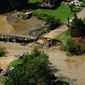 People assess the damage Friday, Sept. 9, 2011, after heavy rainfall on Thursday knocked out Mattox Avenue, opening up Placid Lake into Burnt House Cove in Oak Grove, Va., due to the effects of the remnants of Tropical Storm Lee. (AP Photo/The Free Lance-Star, Dave Ellis)