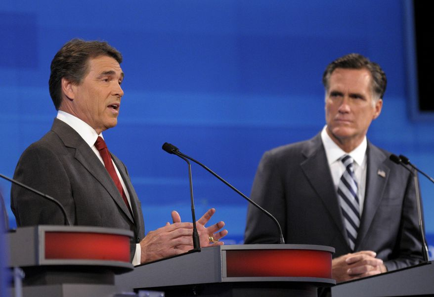 Former Massachusetts Gov. Mitt Romney (right) listens as Texas Gov. Rick Perry makes a statement during a Republican presidential candidate debate on Sept. 22, 2011, in Orlando, Fla. (Associated Press)