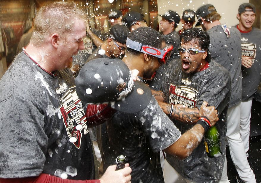 Arizona Diamondbacks' J.J. Putz, left, Chris Young, and Henry Blanco celebrate in the team'S locker room after an MLB baseball game against the San Francisco Giants, Friday, Sept. 23, 2011, in Phoenix. The Diamondbacks defeated the Giants 3-1 and won the 2011 National League West Champions title. (AP Photo/Ross D. Franklin)