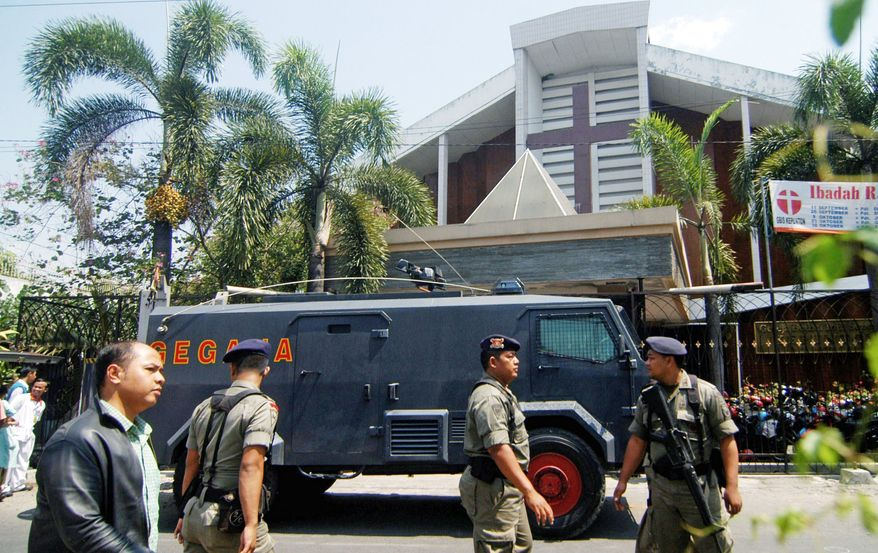 An Indonesian police officer stands guard near an armored vehicle outside a church after an explosion in Solo, Central Java, Indonesia, on Sunday. A suicide bomber attacked the church packed with hundreds of worshippers Sunday, killing himself and wounding at least 22 people, police and hospital officials said. (Associated Press)