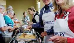 "Former Massachusetts Gov. Mitt Romney, a Republican presidential candidate, and Ann, his wife of 42 years, serve up a Labor Day pancake breakfast in Manchester, N.H., She wears the white apron with the ease of a woman who spent countless mornings flipping flapjacks for five hungry sons. ""It's going to happen this time,"" she said. (Associated Press)"