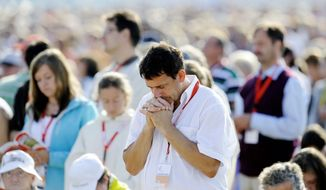 A man prays amid a gathering of about 100,000 faithful during the pope's Mass in Freiburg, Germany. The pope Sunday ended his first state visit to his homeland.