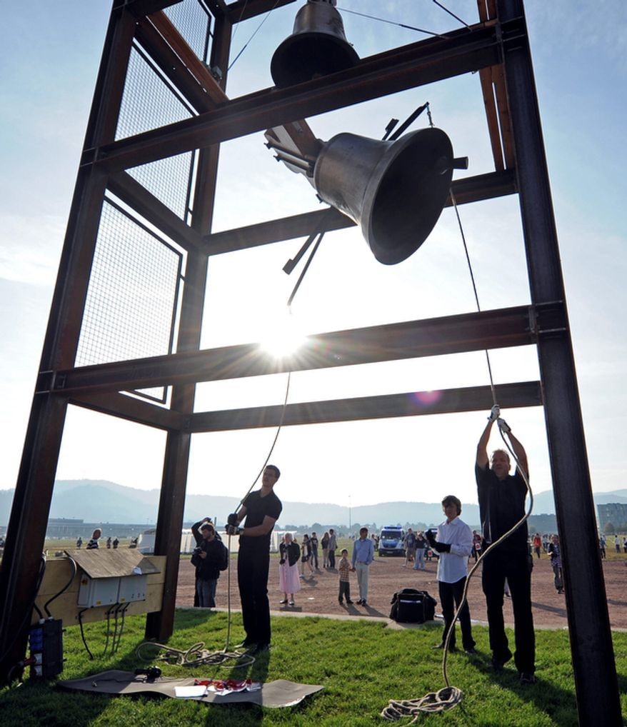 People strike a bell for a mass with Pope Benedict XVI at the airfield in Freiburg, Germany.  (AP Photo/Martin Meissner)