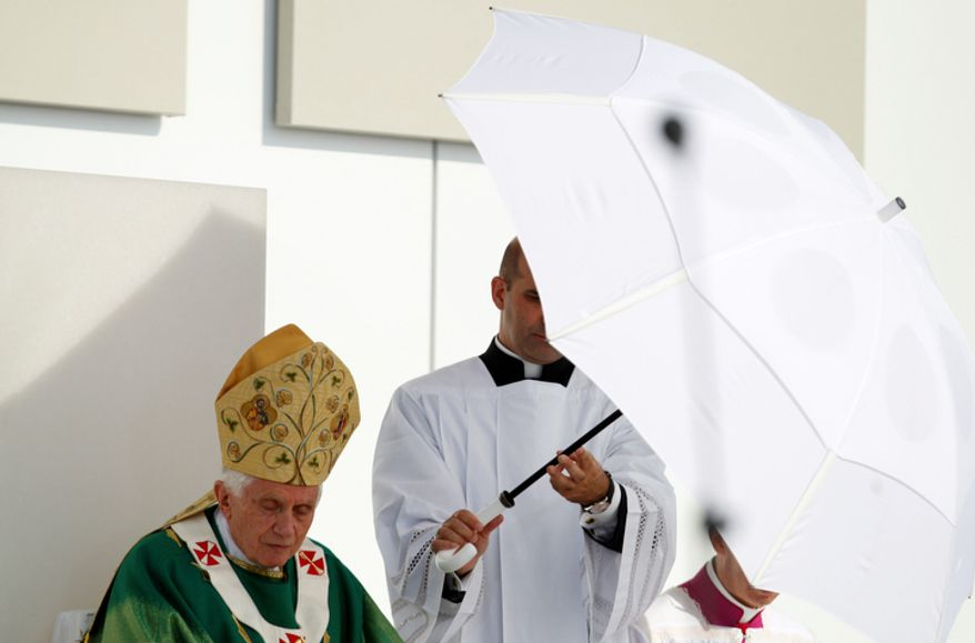 Pope Benedict XVI is shielded against the sun during an open-air mass in Freiburg, Germany, Sunday, Sept.25, 2011, the last day of a four-day-visit to his homeland Germany.(AP Photo/Andrew Medichini)
