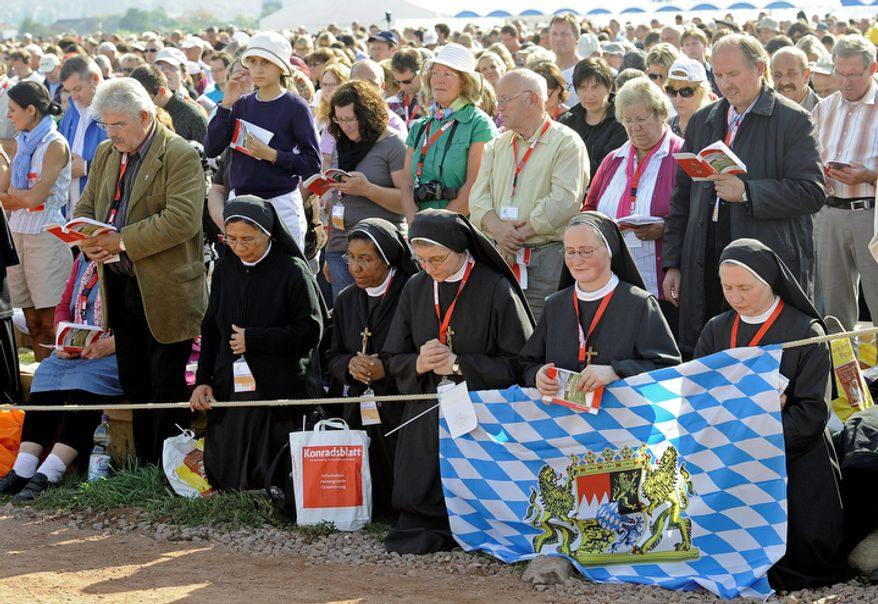 Nuns pray during a mass with Pope Benedict XVI at the airfield in Freiburg, Germany, Sunday, Sept. 25, 2011.   (AP Photo/Martin Meissner)