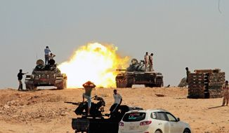 Revolutionary fighters fire from tanks toward Gadhafi troop positions in Sirte, Libya, on Monday. Some civilians trying to flee are stranded on the outskirts due to lack of transportation or fuel. (Associated Press)