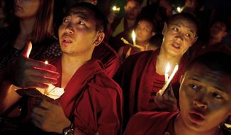 "Exiled Tibetan monks hold a candlelight vigil in Dharmsala, India, as they react to news reports of self-immolation by two Tibetan monks at the Kirti Monastery in China's Sichuan province. The two monks, who are in stable condition after being rescued by police, called out ""long live the Dalai Lama,"" according to Free Tibet. (Associated Press)"