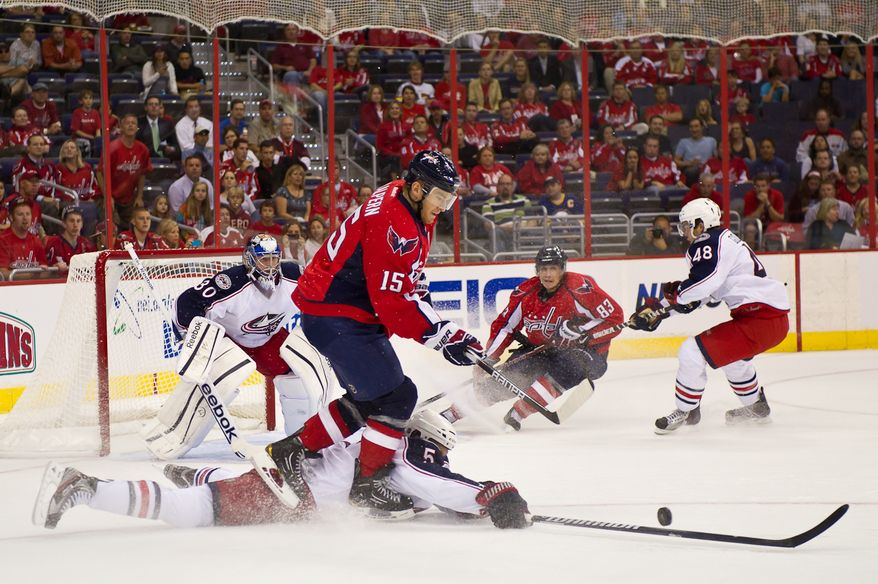 Aaron Johnson (5) of the Columbus Blue Jackets lays out and breaks up a play on goal against Jeff Halpern (15) of the Washington Capitals in the first period in preseason hockey at the Verizon Center in Washington, DC, Monday, September 26, 2011. (Andrew Harnik / The Washington Times)