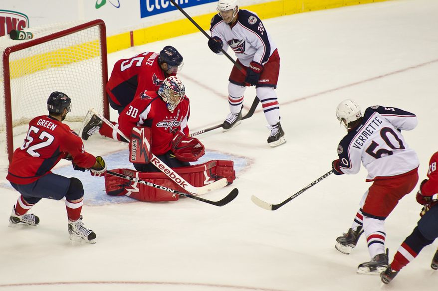 Goaltender Michal Neuvirth (30) of the Washington Capitals blocks a shot on goal by Antoine Vermette (50) of the Columbus Blue Jackets in  the second period in preseason hockey at the Verizon Center in Washington, DC, Monday, September 26, 2011. (Andrew Harnik / The Washington Times)