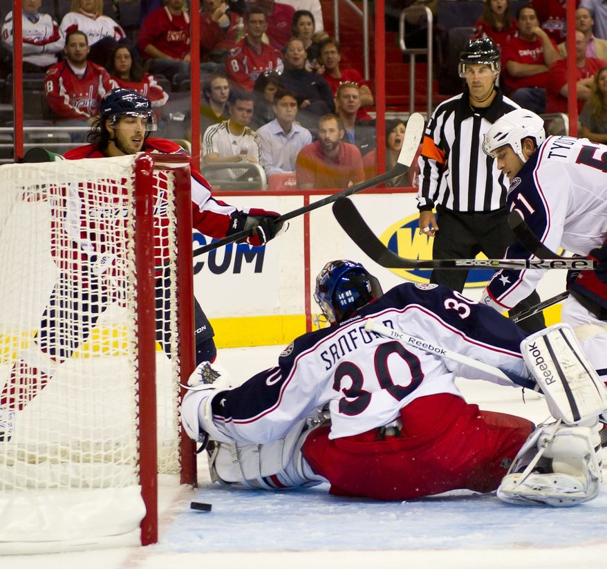 Mathieu Perreault (85) the Washington Capitals, left, scores on goaltender Curtis Sanford (30) of the Columbus Blue Jackets to make the score 3-0 in the second period in preseason hockey at the Verizon Center in Washington, DC, Monday, September 26, 2011. (Andrew Harnik / The Washington Times)