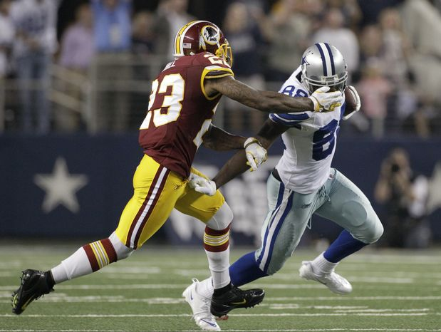 Washington Redskins cornerback DeAngelo Hall grabs Dallas Cowboys wide receiver Dez Bryant's face mask during the second half of an NFL football game Monday, Sept. 26, 2011, in Arlington, Texas. The Cowboys won 18-16. (AP Photo/Tony Gutierrez)