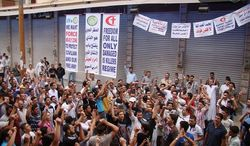 A citizen-journalist says this mobile-phone photo shows a demonstration against Syrian President Bashar Assad held Friday in Homs province. After six months of peaceful insurgency met by severe crackdowns, more protesters are starting to take up arms. (Homs Quarters Union via Associated Press)