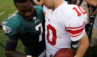 Eagles QB Michael Vick (left) and New York counterpart Eli Manning likely will be in a battle with the Redskins and Cowboys throughout the season. (Associated Press)